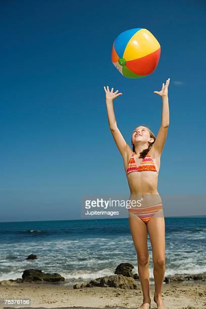 Girl tossing beach ball