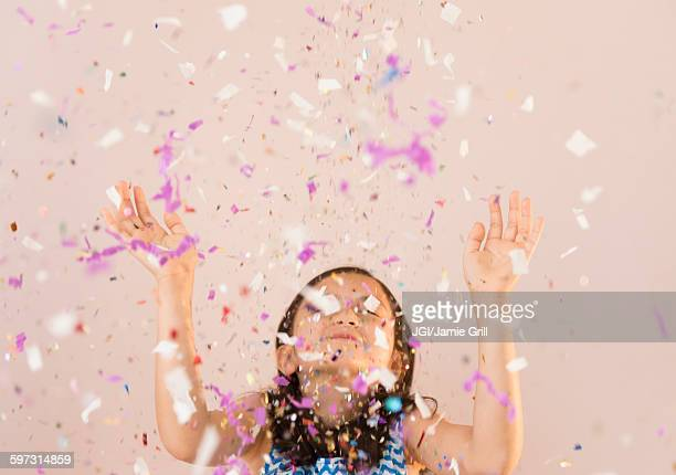 Girl tossing confetti in air