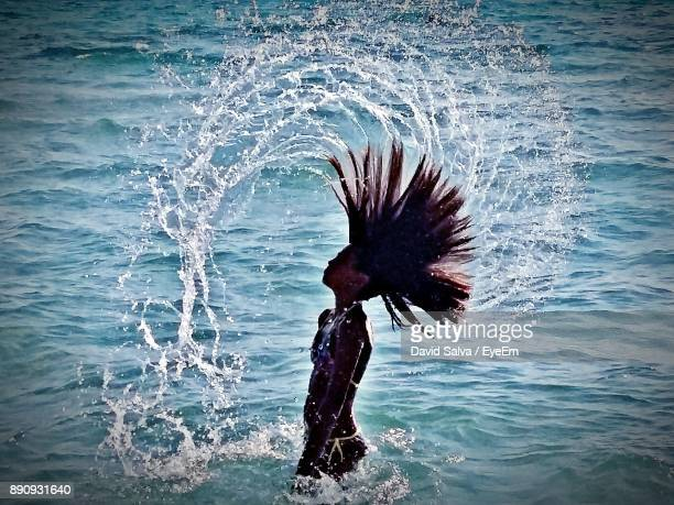 Girl Tossing Hair While Standing In Sea At Beach