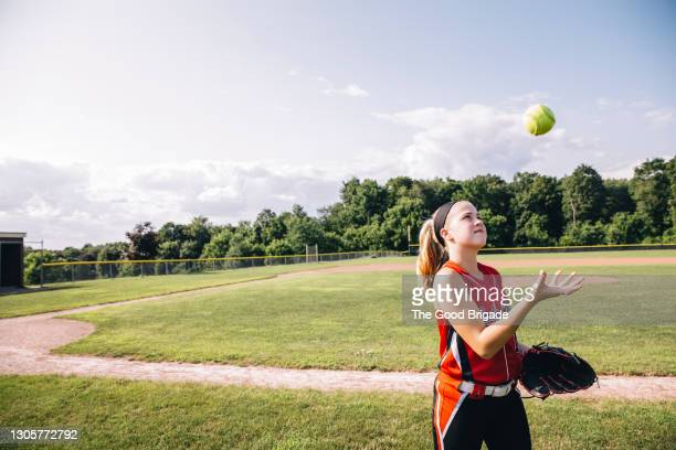 girl tossing softball in air on filed against blue sky - baseball strip stock pictures, royalty-free photos & images