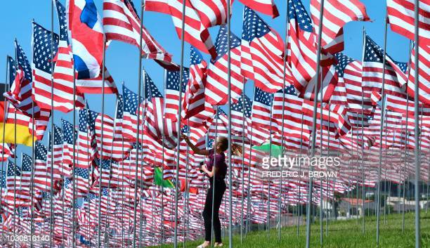 A girl touches a flag as people visit the 'Waves of Flags' display at Pepperdine University in Malibu California on September 10 where the annual...
