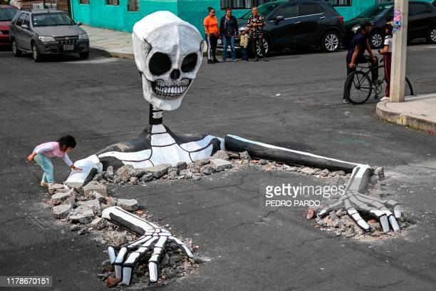 A girl touches a huge cardboard skull made by artisans in a street in the Tlahuac neighborhood in Mexico City on October 28 ahead of the Day of the...