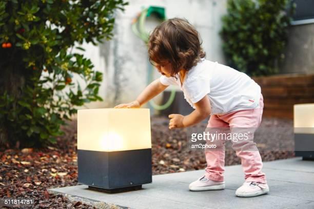 Girl touching a garden lamp