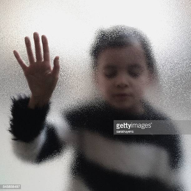 Girl touching frosted glass