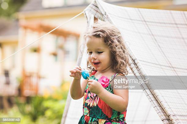 Girl touching ice lolly in garden