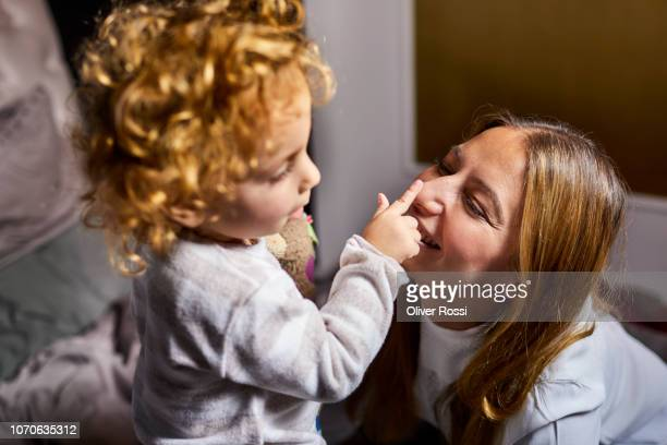 Girl touching mother's nose