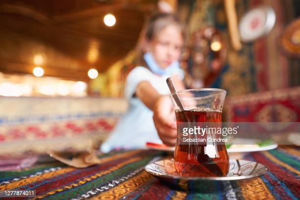 girl tourist drinking delicious traditional turkish tea in outdoor cafe at summer. - tradition stock pictures, royalty-free photos & images