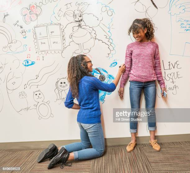 Girl tracing friend on whiteboard