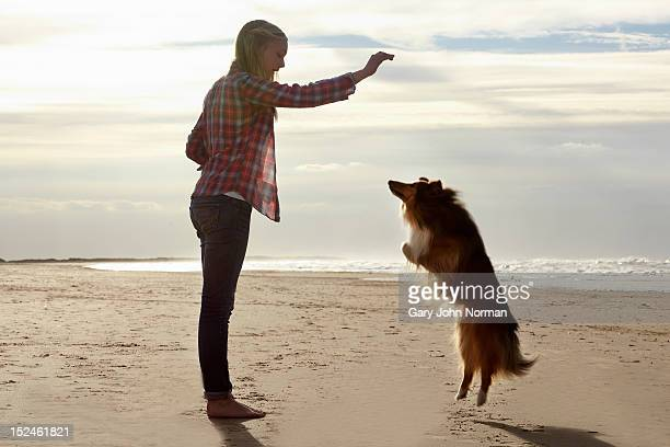 girl ( 14-16) training dog on beach