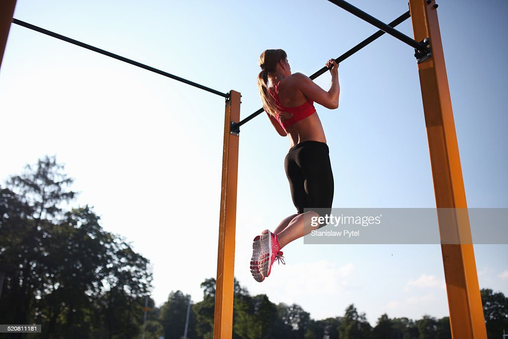 Girl training on chin-up bar outdoor : Stock Photo