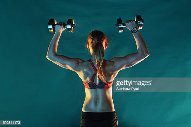 Girl training with dumbbells, back view, green ba