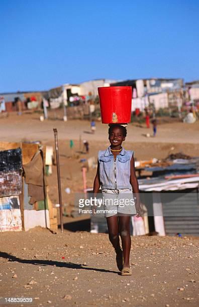 Girl transporting water on head at Goreangab township.