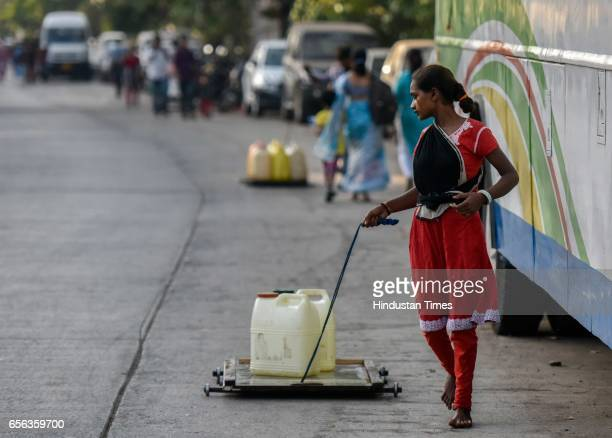A girl transports water on a hand cart on the eve of World Water Day at Mahakali Nagar Worli on March 21 2017 in Mumbai India World Water Day is an...