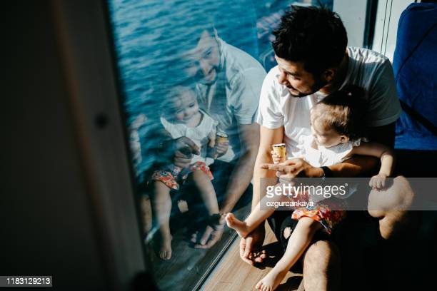 girl traveling by ship with her father and looking through the window - ferry stock pictures, royalty-free photos & images