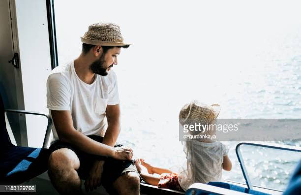 girl traveling by ship with her father and looking through the window - passenger craft stock pictures, royalty-free photos & images