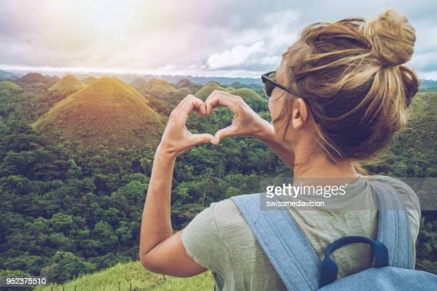 meisje reizen maakt hart op chocolade heuvels van bohol, filippijnen - bewondering stockfoto's en -beelden