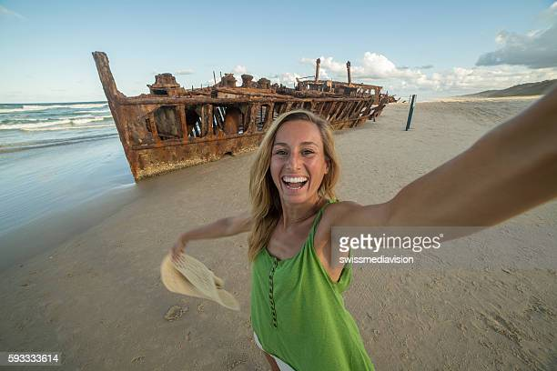 girl traveling takes selfie portrait with shipwreck on fraser island - one young woman only stock pictures, royalty-free photos & images