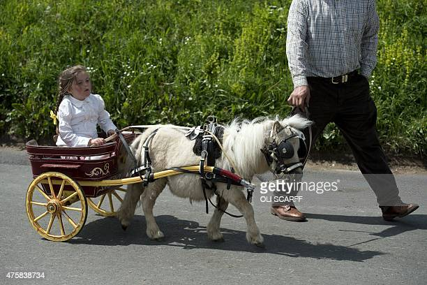 A girl travels in a miniature horsedrawn carriage on the opening day of the annual Appleby Horse Fair in the town of ApplebyinWestmorland North West...