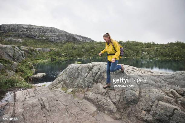 Girl trekking , rocks, lake and forest in background