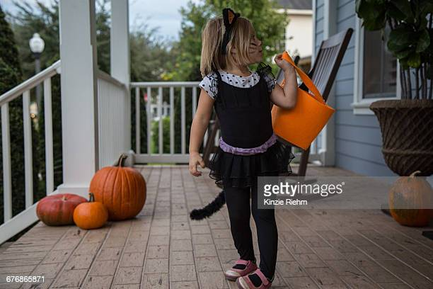 girl trick or treating in cat costume looking over her shoulder on porch - cat costume stock photos and pictures