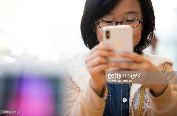 A girl tries an iPhone X at the Apple Omotesando store on November 3 2017 in Tokyo Japan Apple launched the latest iPhone featuring face recognition...