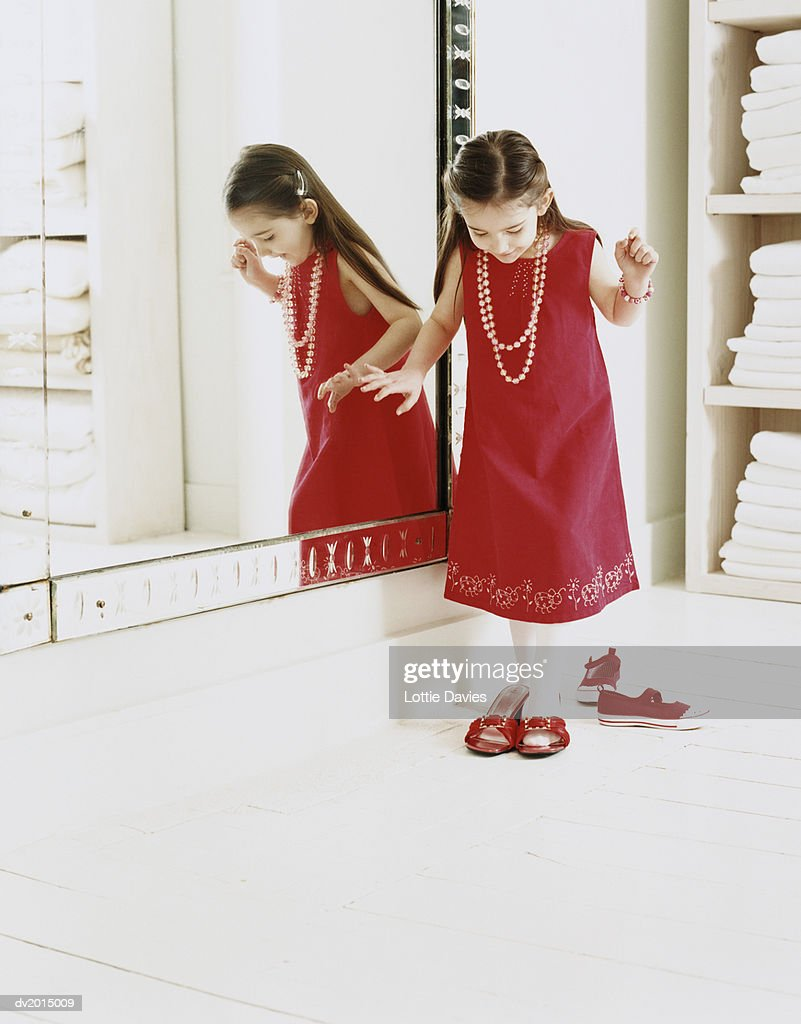 Girl Trying on Adult Shoes Standing by a Mirror : Stock Photo