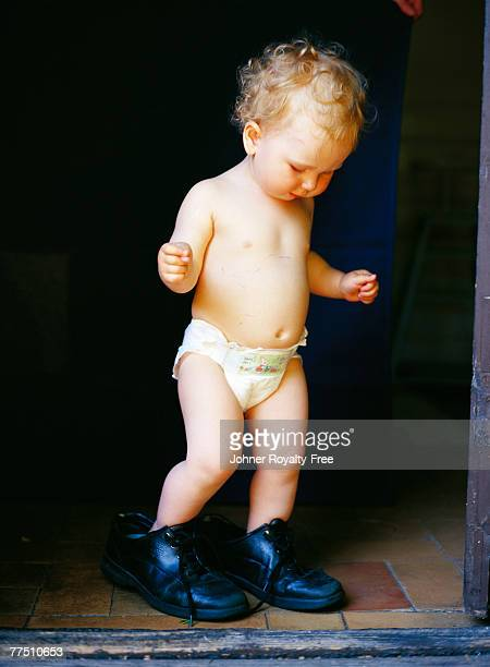 A girl trying on big shoes.