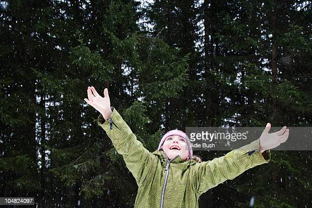Girl trying to catch snowflakes