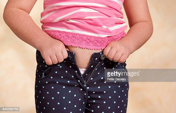 girl trying to do up trousers - fat girls stock photos and pictures