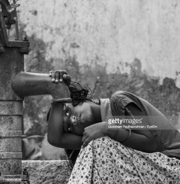 girl trying to drink water from hand pump against wall - drought stock pictures, royalty-free photos & images