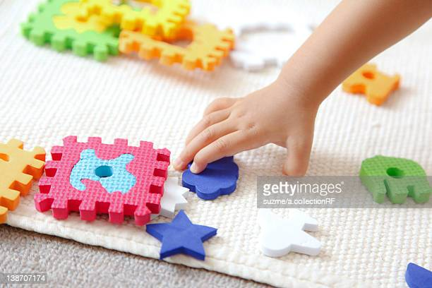 Girl trying to hold a piece of puzzle