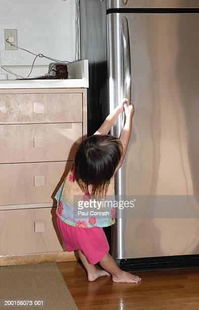 Girl (2-4) trying to open refrigerator door, rear view
