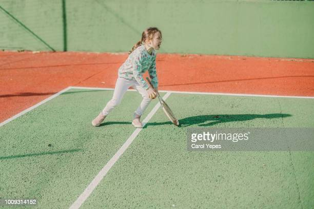 girl trying to play tennis in sunny day