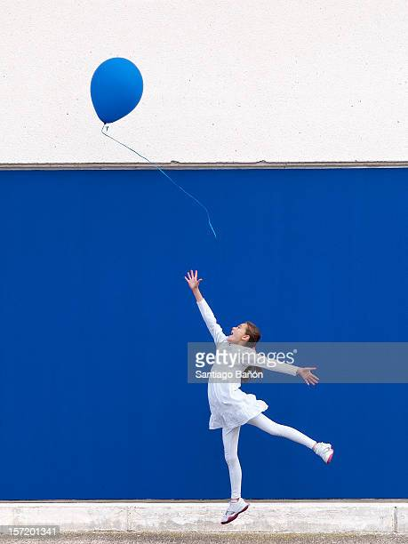 Girl trying to reach blue balloon