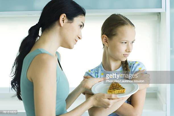 Girl turning head from woman holding piece of quiche