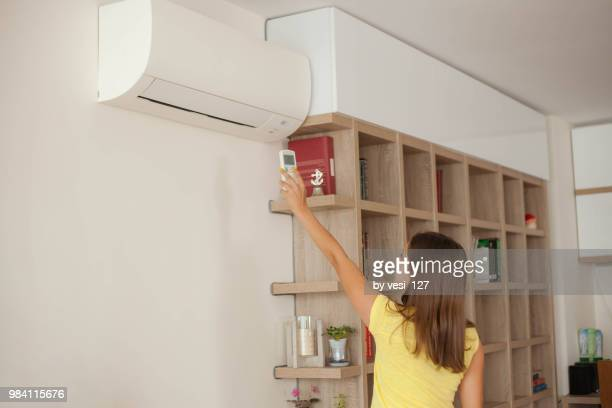 Girl turning on wall mounted air-conditioner at home