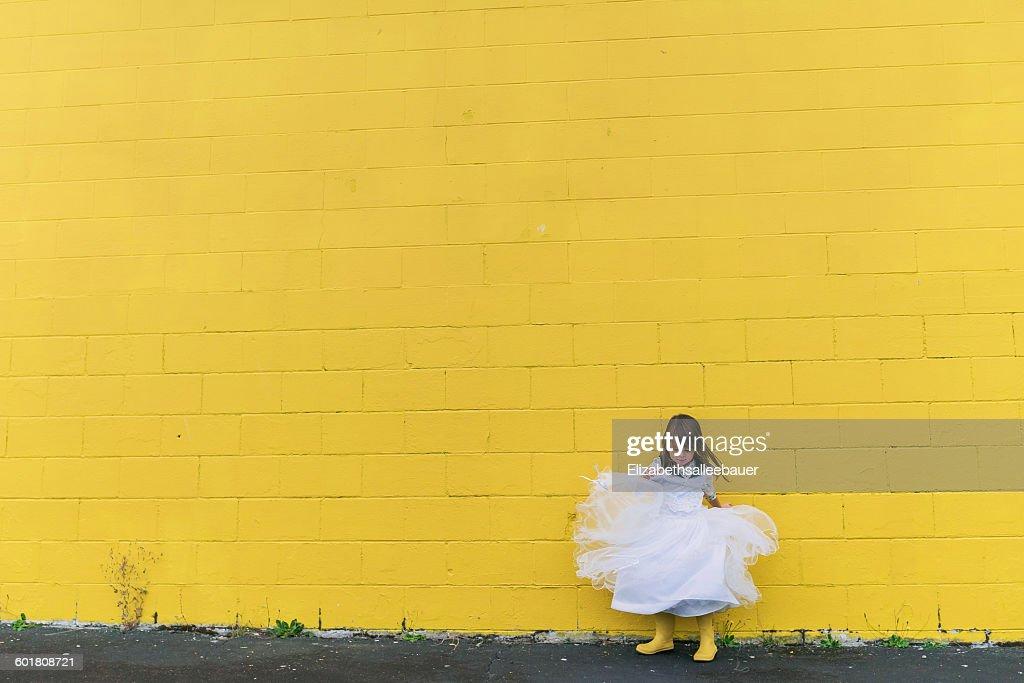 Girl twirling in dress by yellow wall : Foto de stock