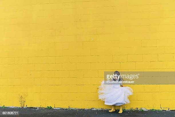 Girl twirling in dress by yellow wall