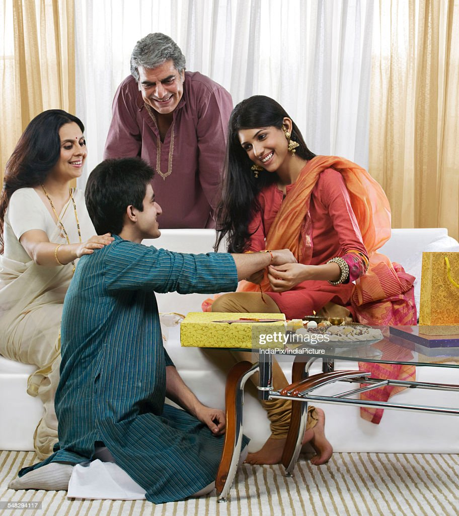 Girl tying a rakhi on her brothers hand : Stock Photo