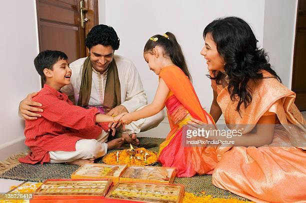 girl tying a rakhi - raksha bandhan stock photos and pictures