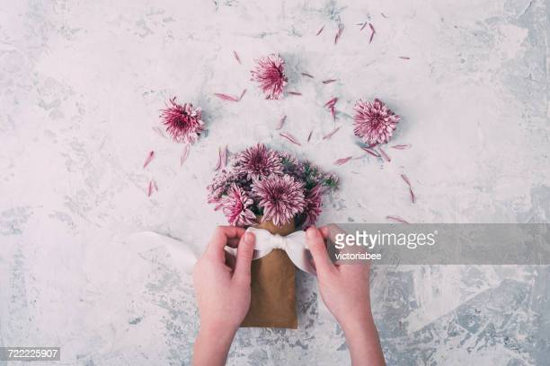 Girl tying bow  around bouquet of pink flowers