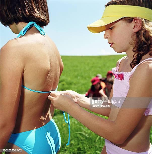 girl (8-10) tying friend's bikini at back, outdoors, side view - 10 11 anni foto e immagini stock