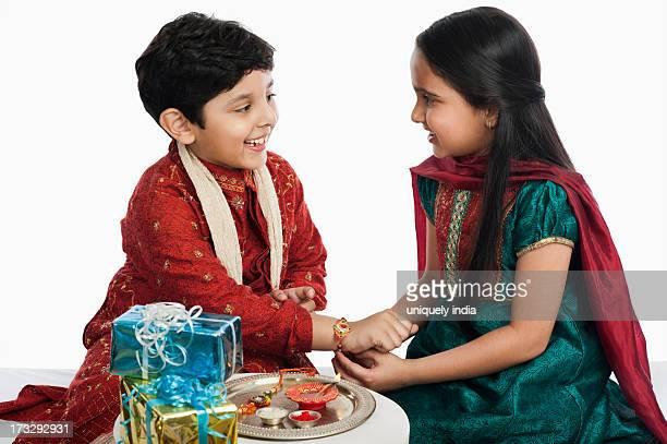 girl tying rakhi on her brother wrist - raksha bandhan stock photos and pictures