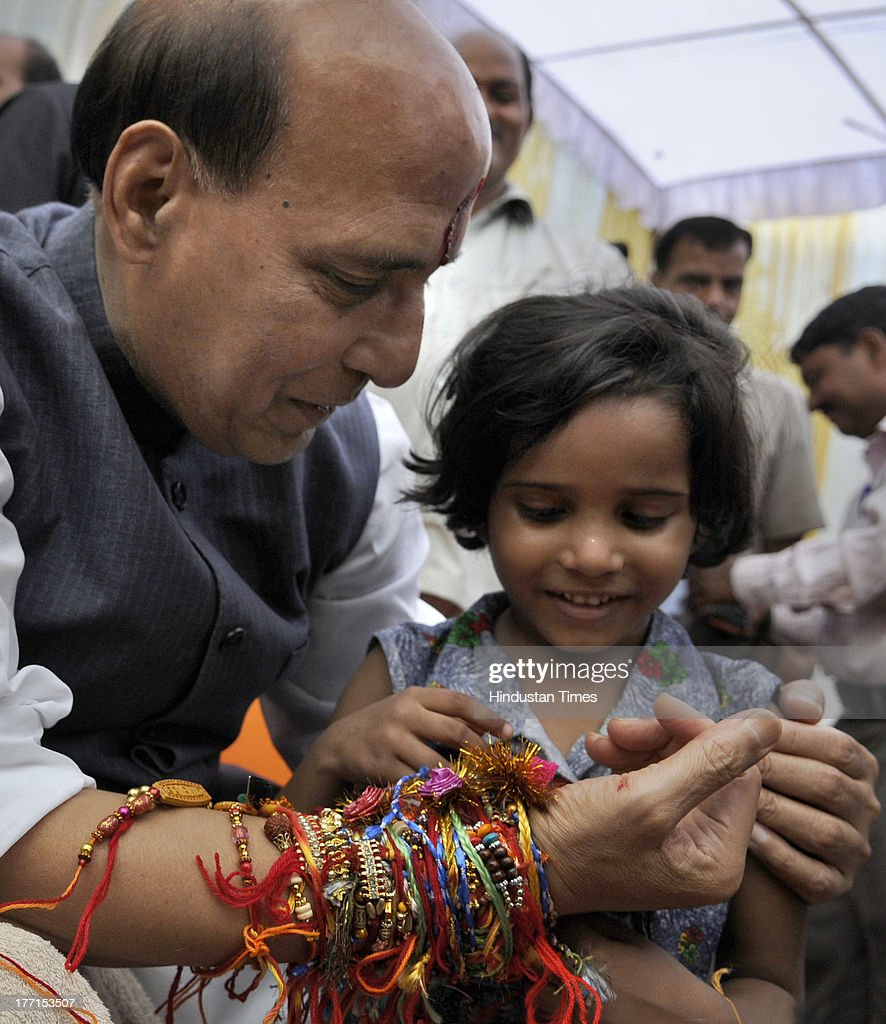 A girl tying Rakhi on the wrist of BJP President Rajnath Singh on the occasion of Rakhi festival at his house on August 21, 2013 in New Delhi, India. Raksha Bandhan, the festival of love between brothers and sisters, is being celebrated across the country today with full enthusiasm.