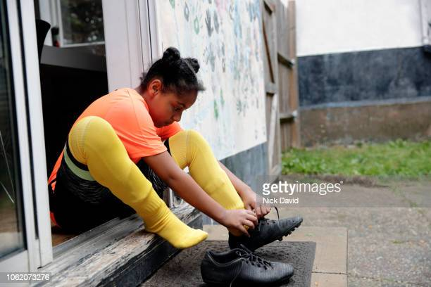 Girl tying up her football  boot laces on back doorstep