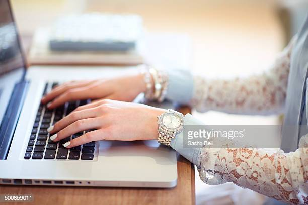 Girl typing on laptop with white nails