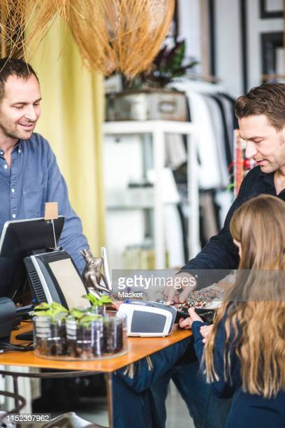 girl typing pin code at checkout counter in clothing store by father - 40s pin up girls stockfoto's en -beelden