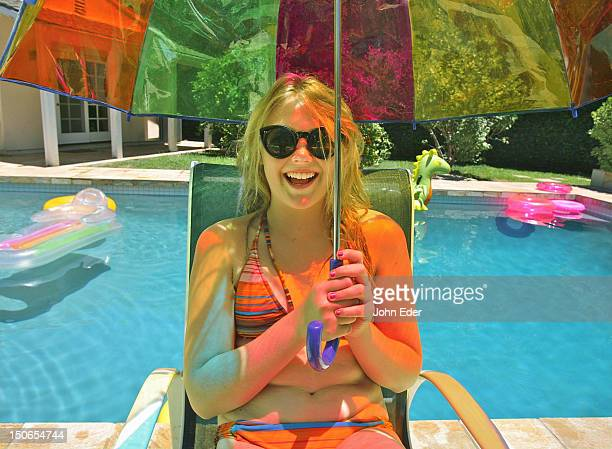 Girl under a colorful umbrella by a pool