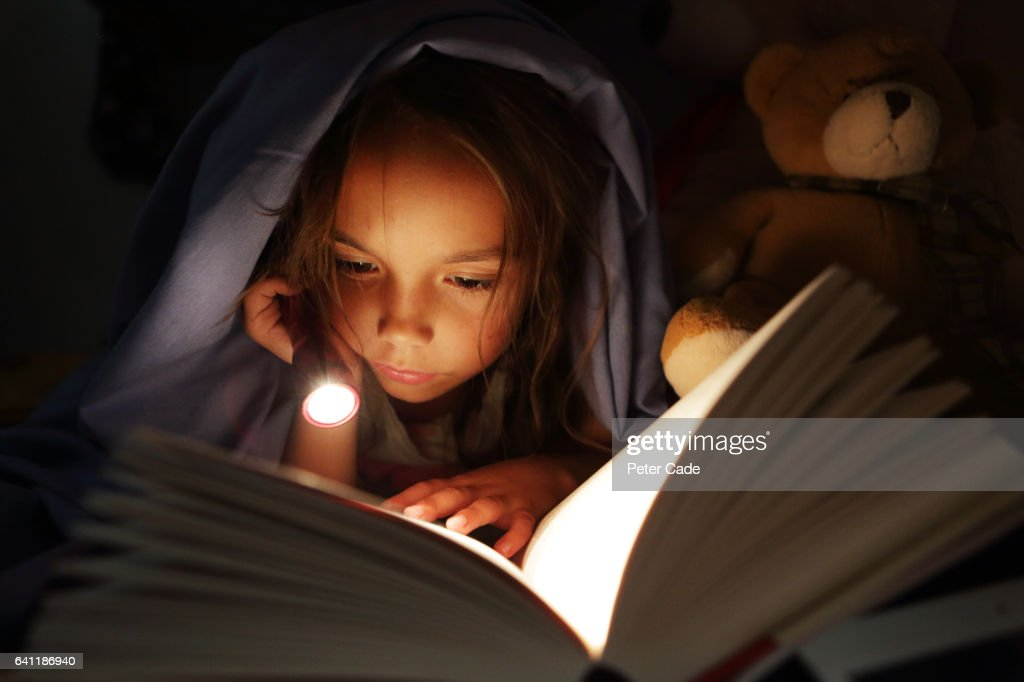 Girl under bed covers reading book by torchlight : Stockfoto