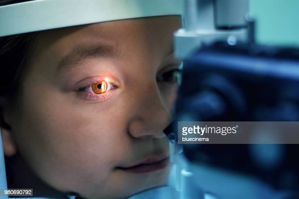 girl undergoing eye examination - eye test equipment stock pictures, royalty-free photos & images